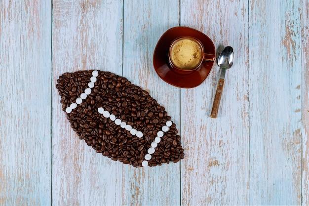 Ballon de football américain à base de grains de café avec une tasse de café frais