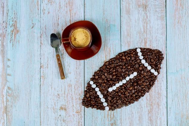 Ballon de football américain fabriqué à partir de grains de café avec une tasse de café frais sur une surface en bois bleue.