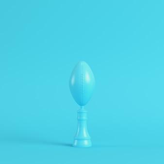 Ballon de football américain throphy sur fond bleu vif dans des couleurs pastel