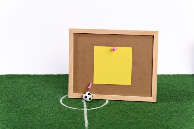 Ballon de football au centre du terrain de football et tableau des résultats