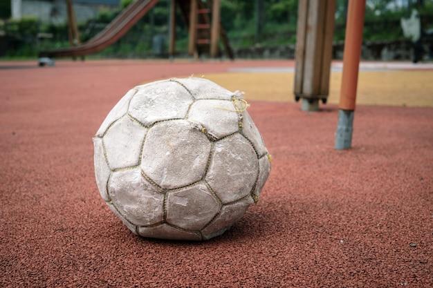 Ballon de football blanc endommagé sur le terrain de jeu