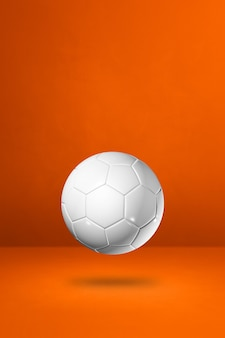 Ballon de football blanc isolé sur fond orange de studio.