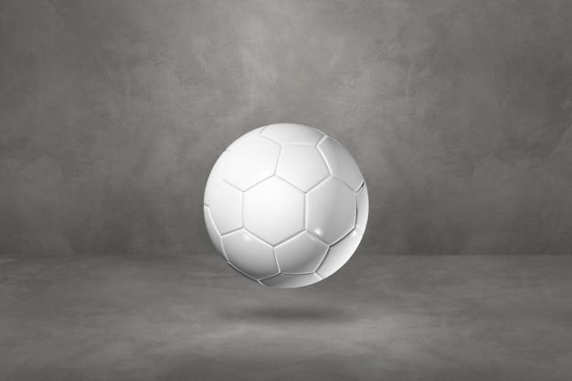 Ballon de football blanc isolé sur un fond de studio en béton.