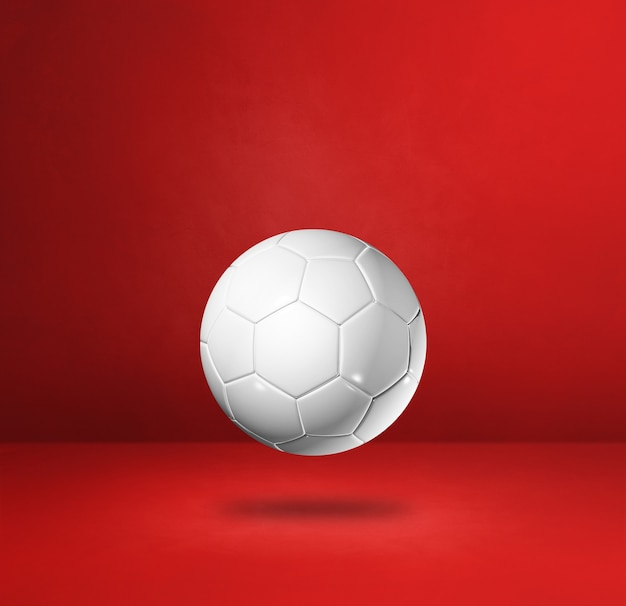 Ballon de football blanc isolé sur fond de studio rouge.