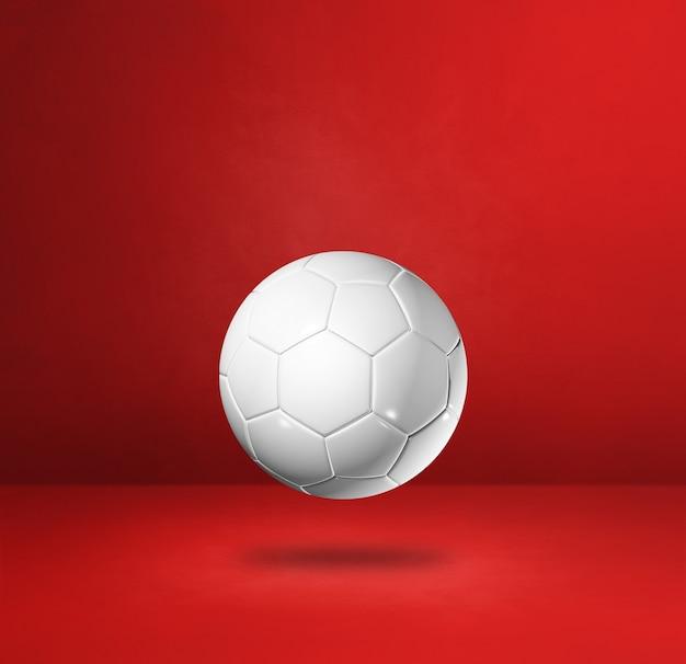 Ballon de football blanc isolé sur fond de studio rouge.
