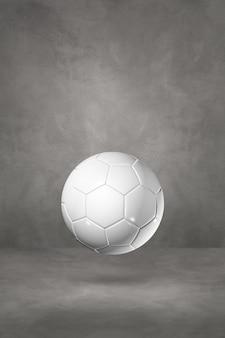 Ballon de football blanc isolé sur un studio en béton