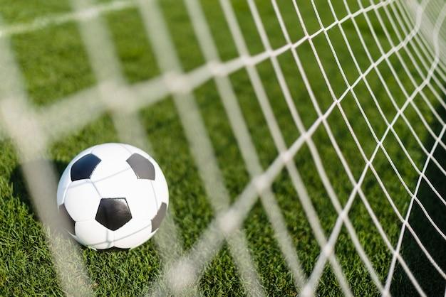 Ballon de football derrière le filet