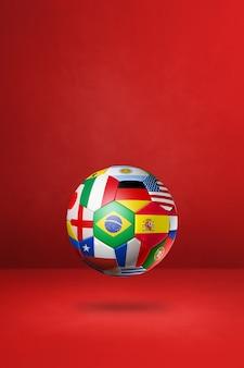 Ballon de football de football avec des drapeaux nationaux isolés sur un fond de studio rouge.