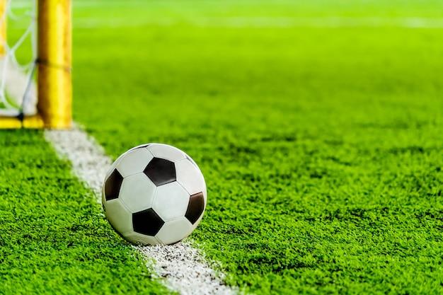 Ballon de football de football noir et blanc classique sur la ligne de but du terrain d'entraînement avec objectif