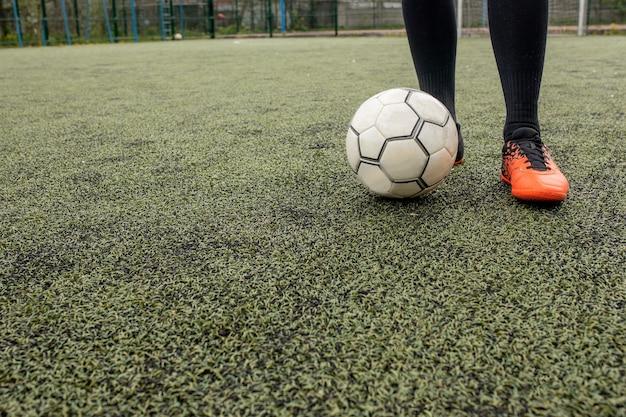 Ballon de football avec ses pieds sur le terrain de football.