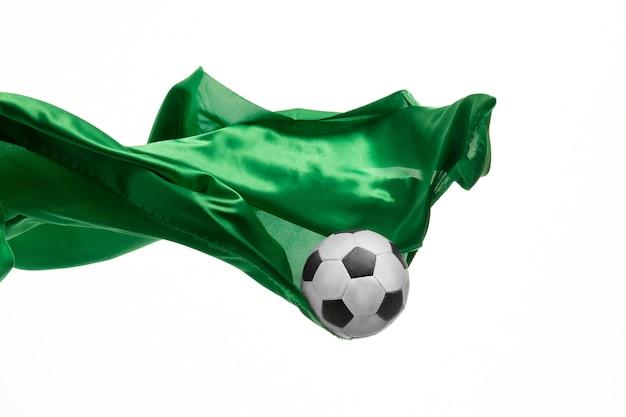 Ballon de football et tissu vert transparent élégant et lisse isolé ou séparé sur fond de studio blanc.