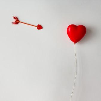 Ballon en forme de coeur rouge avec flèche de cupidon sur une surface blanche