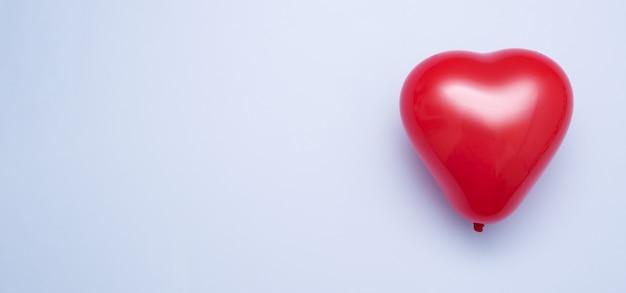 Ballon en forme de coeur rouge sur fond bleu - minimalisme concept saint valentin