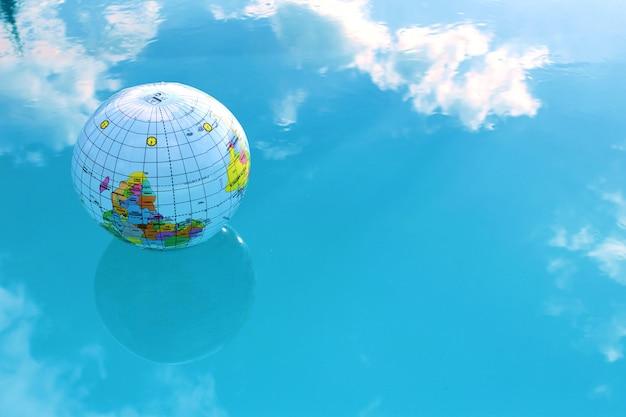 Ballon gonflable en forme de globe dans l'eau bleue