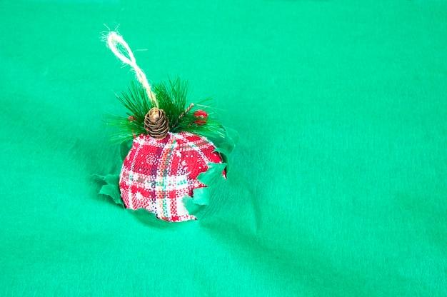 Ballon de noël rouge traverse un fond de papier vert