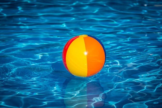 Ballon de plage dans la piscine concept de vacances d'été