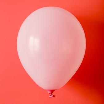 Ballon rose sur fond rouge