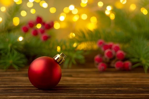 Ballon rouge avec une composition festive d'épinette et de baies de rowan sur une surface en bois. surface floue avec des lumières bokeh. le concept de noël et du nouvel an. la netteté sélectionnée.