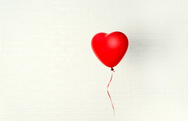 Ballon rouge en forme de coeur accroché à un mur blanc