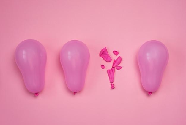 Un ballon sauté parmi d'autres ballons roses entiers sur table rose. concept d'épuisement professionnel ou d'être sous pression. vue de dessus à plat.