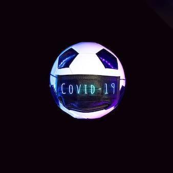 Un ballon de soccer dans un masque médical noir contre le virus. à la lumière du néon sur fond sombre