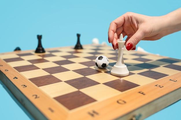 Ballon de soccer de pièces d'échecs sur le plateau