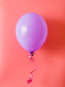 Ballon violet sur fond rose