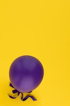 Ballon violet isolé sur fond jaune. ballon violet vibrant dans le coin inférieur. copiez l'espace.