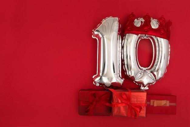 Ballons à air en aluminium argenté montrant le numéro 10 dix placés sur fond rouge avec des cadeaux emballés pour le concept d'anniversaire d'anniversaire