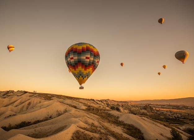 Ballons à air chaud sur les collines et les champs pendant le coucher du soleil en cappadoce, turquie
