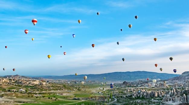 Ballons à air chaud colorés survolant un paysage rocheux en turquie cappadoce