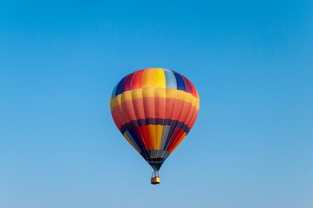 Ballons à air chaud colorés volant dans le ciel bleu