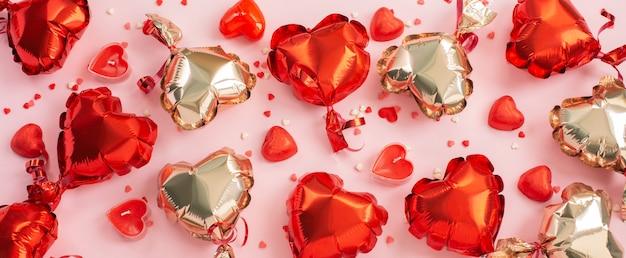 Ballons à air en forme de coeur, bonbons et bougies sur un rose.
