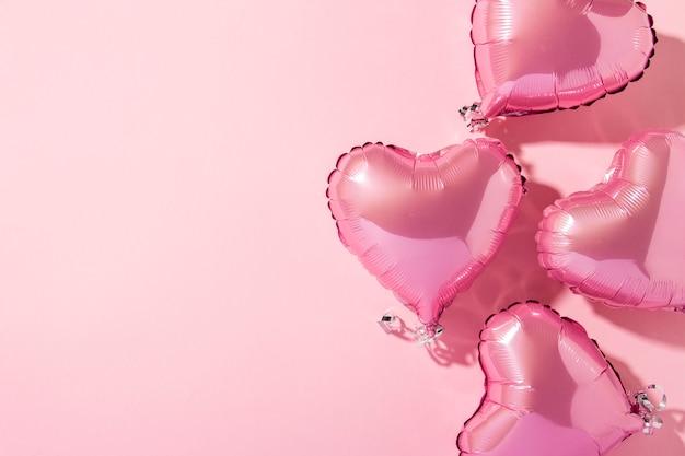 Ballons à air en forme de coeur sur fond rose. lumière naturelle. bannière. amour, mariage, zone photo. mise à plat, vue de dessus