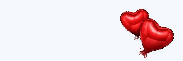 Ballons à air rose en forme de coeur sur une surface blanche