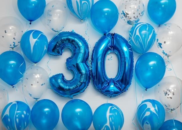 Ballons en aluminium de célébration numéro 30 bleu avec des ballons d'hélium sur blanc.