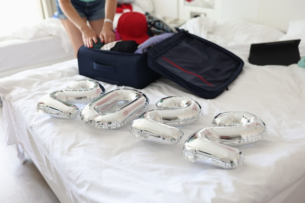 Ballons d'argent avec des nombres allongés sur le lit avec une valise dans la chambre en gros plan