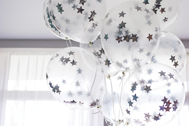 Ballons blancs volants avec des étoiles d'argent sous le plafond