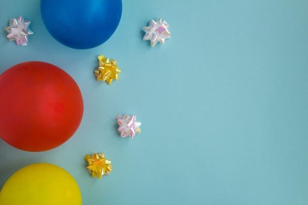 Ballons colorés et confettis sur fond bleu