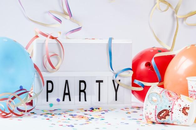 Ballons colorés avec des confettis en papier et un panneau de lampe à led avec [party] écrit dessus