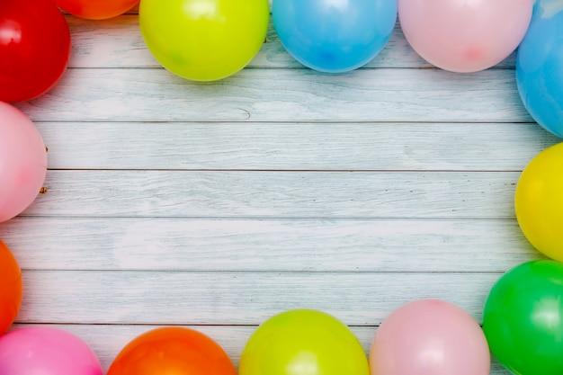 Ballons colorés et confettis sur la vue de dessus de table en bois. contexte de fête ou de fête. style plat laïc. carnaval.