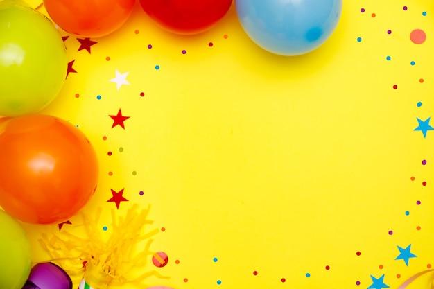 Ballons colorés et confettis sur la vue de dessus de table jaune. contexte de fête ou de fête. style plat laïc. carnaval.
