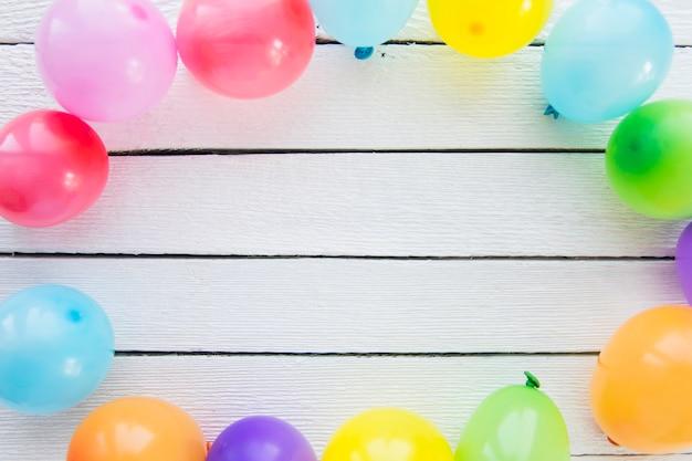 Ballons colorés décorés sur une planche en bois blanche