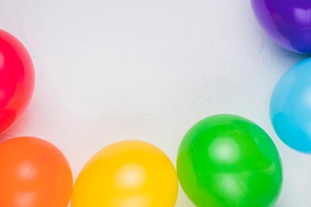 Ballons colorés disposés sur une surface blanche