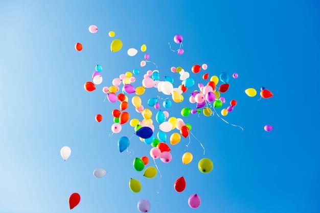 Ballons colorés lumineux sur ciel bleu
