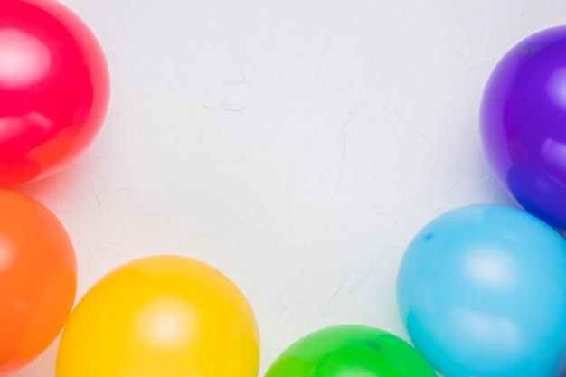 Ballons colorés sur une surface blanche