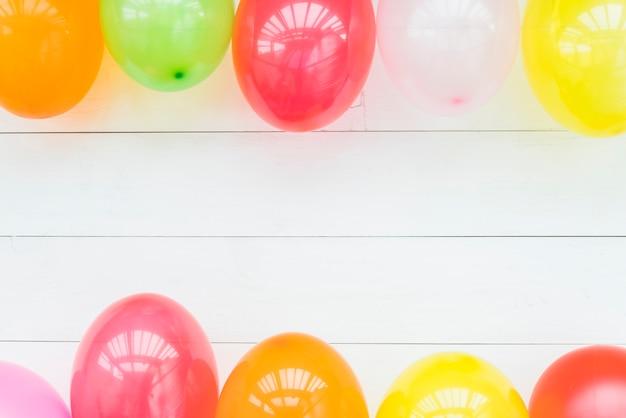 Ballons colorés sur une table en bois blanche