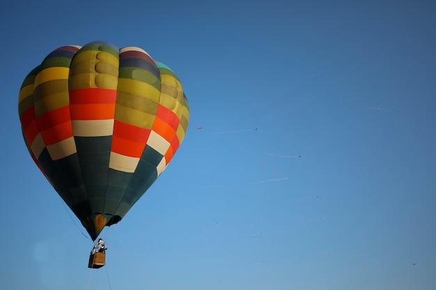 Ballons de couleurs vives flottant dans le ciel bleu.