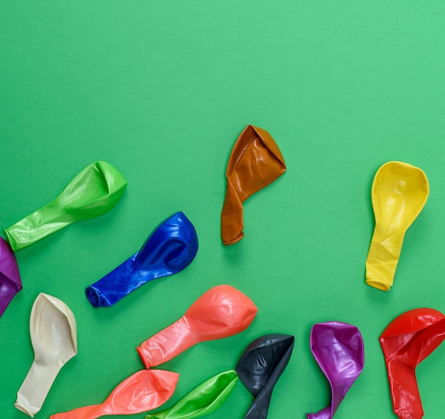 Ballons dégonflés colorés sur vert