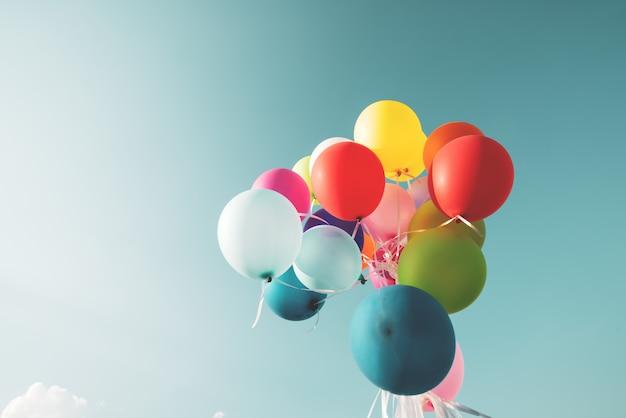 Ballons festifs colorés sur un ciel bleu avec un effet de filtre rétro instagram vintage.